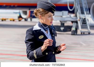 Russia, Vladivostok, 10/13/2017. Beautiful stewardess dressed in official dark blue uniform of Aeroflot Airlines on airfield. Passenger plane on background. Crew of plane. Aviation and transportation.
