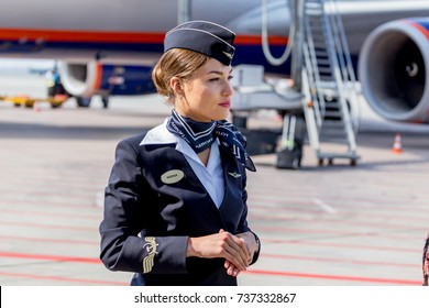 Russia, Vladivostok, 10/13/2017. Beautiful stewardess dressed in official dark blue uniform of Aeroflot Airlines on airfield. Passenger plane on background. Crew of plane. Aviation and transportation.