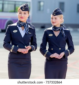 Russia, Vladivostok, 10/13/2017. Beautiful stewardesses dressed in official dark blue uniform of Aeroflot Airlines on airfield. Passenger plane on background. Plane's crew. Aviation and transportation