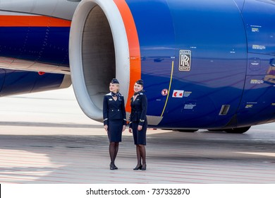 Russia, Vladivostok, 10/13/2017. Beautiful stewardesses dressed in official dark blue uniform of Aeroflot Airlines stand near at Rolls Royce's engine of plane. Plane' crew. Aviation and transportation