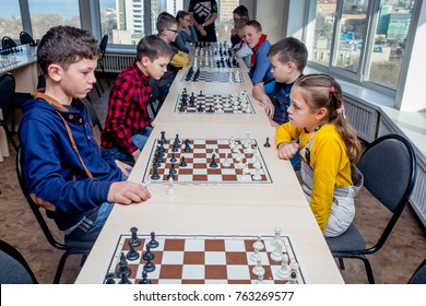Russia, Vladivostok, 11/25/2017. Kids play chess during chess competition in chess club. Education, chess and mind games. Competition and tournament. Kids' leisure.