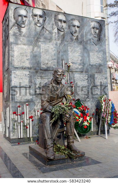 Russia, Vladivostok, 20/02/2017. Monument to dead warriors. Warrior with machine gun sitting at wall with inscriptions in Russian. Some natural flowers lie on monument, wreaths stand at the wall.