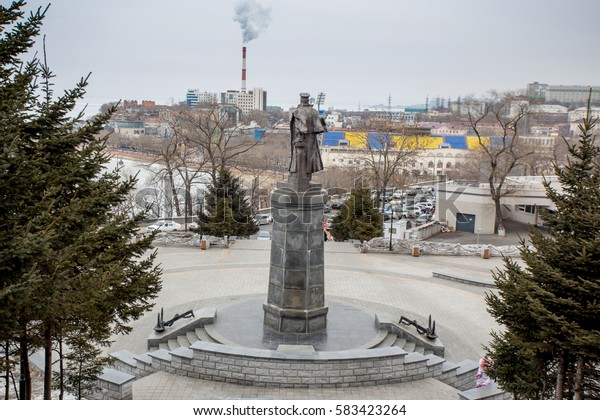 Russia, Vladivostok, 20/02/2017. Monument in the glory of Russian vice-admiral S. Makarov, back view. Embankment of Vladivostok with smoking chimney is on background