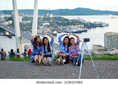 Russia, Vladivostok, June 11, 2018. Korean tourists doing selfie on the background of a beautiful view of the city of Vladivostok