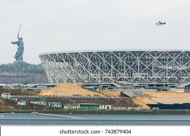 Russia, Volograd, 28 October 2017. Transport helicopter flying over the construction site of the Volgograd Arena stadium. On the left hand - monument The Motherland Calls at the top of th? Mamaev Hill