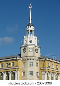 Russia, Voronezh. The big yellow building with a high spike on a roof and hours, against the dark blue sky, a sunny day