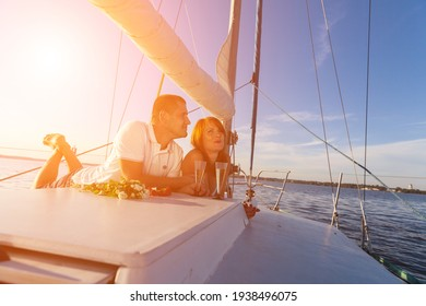 Russia. Vyborg. 08.08.2013 Beautiful couple sail on a yacht in the summer at sunset. High quality photo