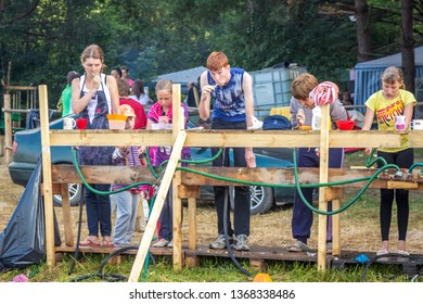 RUSSIA, YAROSLAVL - 03 JULY 2014: group children and adult teens brushing  teeth early morning in summer forest tent camp on banks Volga river participate in competitions on bright Sunny day