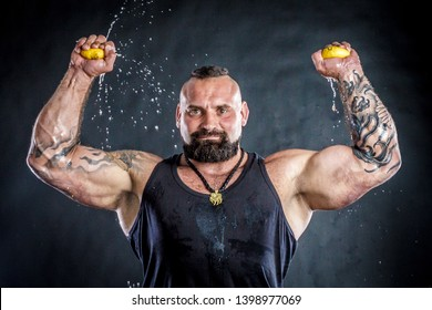 RUSSIA, YAROSLAVL - 14 SEP. 2018: strong man with muscles crushes lemon with hands from which juice flows in studio with isolated black background. the concept of crazy freak chef in kitchen