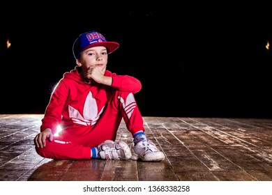 RUSSIA, YAROSLAVL - 16 JAN. 2016: young funny dancer kid in red adidas suit and blue cap sits on stage of theater in the backlit flash