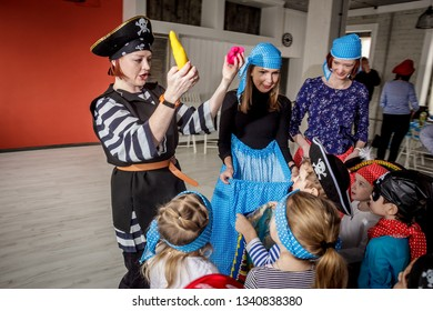 RUSSIA, YAROSLAVL - 17 FEB. 2018: happy group of children at a birthday celebration dressed in the style of pirates with an animator, contests and bubbles play games in a large room with loft style