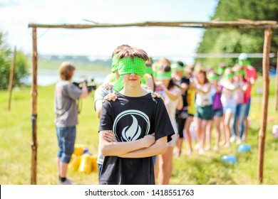 RUSSIA, YAROSLAVL - 30 JUN 2012: group happy children and adult teens relax in summer forest tent camp play active games on banks Volga river participate in competitions on bright Sunny day