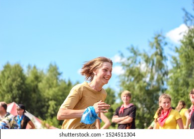 RUSSIA, YAROSLAVL - 30 JUN 2012: group happy children and adult teens relax in summer forest tent camp play active games on banks Volga river participate in run competitions on bright Sunny day