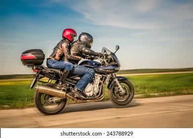 RUSSIA-JULY 7, 2013: Man and woman on a Suzuki Bandit bike doing wheelies. Suzuki Bandit is a series of sport-standard motorcycles. Suzuki Motor Corporation is a Japanese multinational corporation.