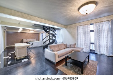 Russia,Moscow - modern living room interior. Duplex apartment with a stylish spiral staircase.