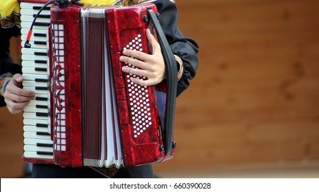 The Russian accordion player plays in the park.