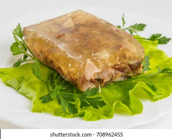 Russian aspic jelly with greens on a white plate.