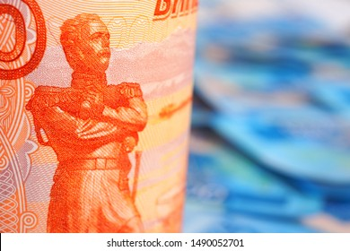A Russian banknote of 5000 rubles stands on a field of banknotes of 2000 rubles. A fragment of a 5000-ruble banknote shot close-up. A field of banknotes of 2000 rubles forms a blue background