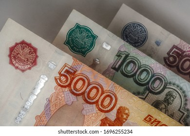 Russian banknotes of 5000, 1000, and 500 rubles are hanging over a gray background. Dark, gloomy illustration on the theme of money, finance and economics. Aged effect shot. Top view. Close-up - Shutterstock ID 1696255234