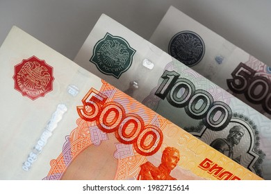 Russian banknotes 5000, 1000 and 500 rubles close up. Bright expressive illustration about economy and money of Russia. Nearest bill is highlighted in vivid color, other notes are pale. Macro - Shutterstock ID 1982715614