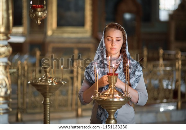 Russian beautiful Caucasian woman with red hair and a scarf on her head is in the Orthodox Church, lights a candle and prays in front of the icon