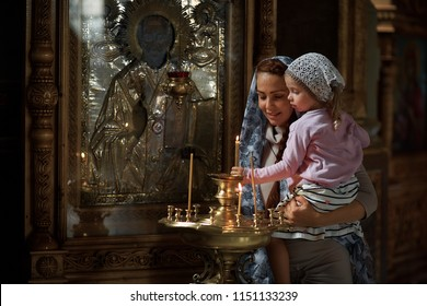 Russian beautiful woman in a scarf and with red hair holding a little girl and lights a candle in front of an icon in the Russian Orthodox Church.