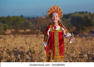 Russian beauty, emotional girl in traditional folk Russian costume and headdress adorable smiling and laughing