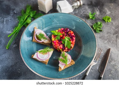 Russian beetroot salad vinaigrette with fish on bread in a plate