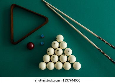 Russian billiard balls, cue, triangle, chalk on a table. Green cloth. Top view