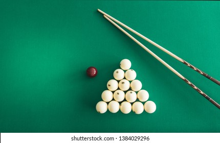 Russian billiard balls, cue, triangle, chalk on a table Green cloth Top view Copy space
