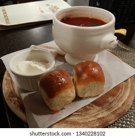 Russian borsch in a bowl, two buns and sour cream