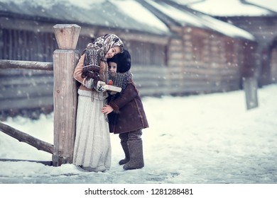Russian brother and sister are hugging each other and holding a cage with a bullfinch in russian village in winter. Image with selective focus and toning