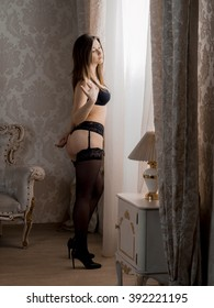 Russian brunette girl with big breasts in black lingerie, stockings and heels standing in the bedroom near the window