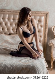 Russian brunette girl with big breasts in black lingerie, stockings and heels posing on the bed