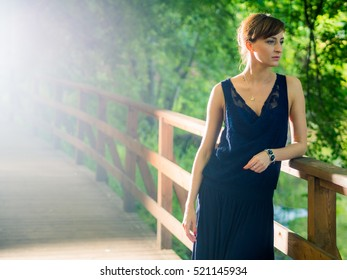 Russian brunette girl in a long dress on a bridge in the forest in the background of the river