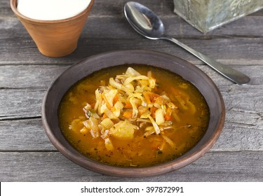 Russian cabbage soup in clay plate on a dark wooden background