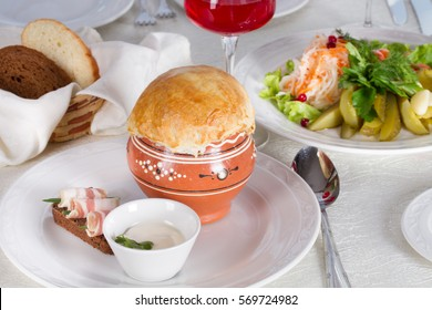 Russian cabbage soup in a clay pot baked dough and sandwich with bacon