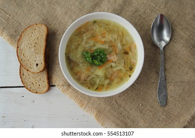 Russian cabbage soup (Shchi) in ceramic bowl with bread and spoon