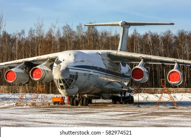 Russian cargo aircraft is parked on the ground parking place an the maintenance. Whole aircraft covered with snow.