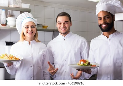 russian chef and his assistants preparing meal in tavern
