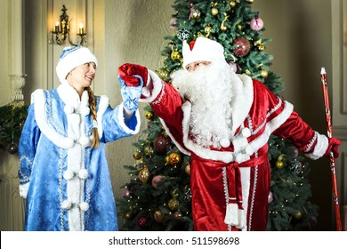 Russian Christmas characters: Ded Moroz (Santa) and Snegurochka (snow girl) around the Christmas tree
