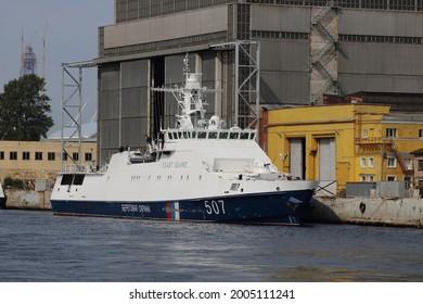 Russian Coast Guard ship moored to the pier, lettering on board Beregovaya okhrana (Coast Guard)