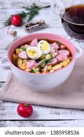 Russian cold soup Okroshka with vegetables, sausage, eggs and kvass in a ceramic bowl on the white table