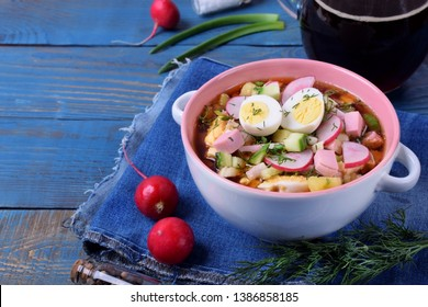 Russian cold soup Okroshka with vegetables, sausage, eggs and kvass in a ceramic bowl on the blue table