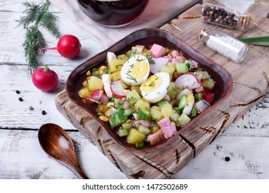 Russian cold soup Okroshka with vegetables, sausage, eggs and kvass in wooden bowl on white table