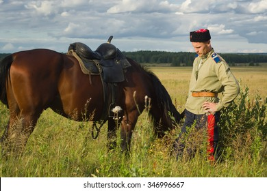 Russian Cossack and a horse resting in the summer field
