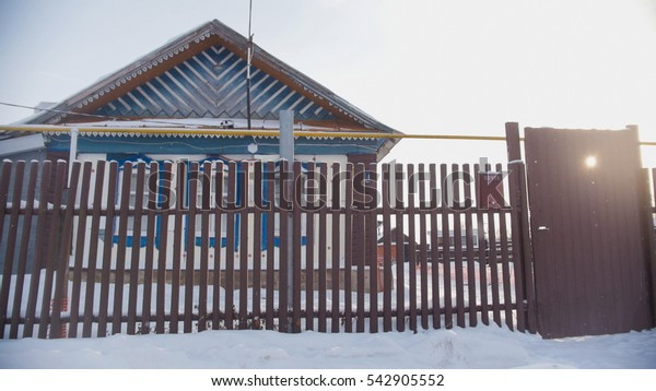Russian country - typical cottage in a snow-covered empty village at sunny day, wide angle