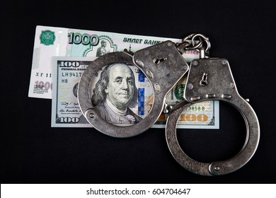 Russian Currency with Dollars and Handcuffs on the Black Background