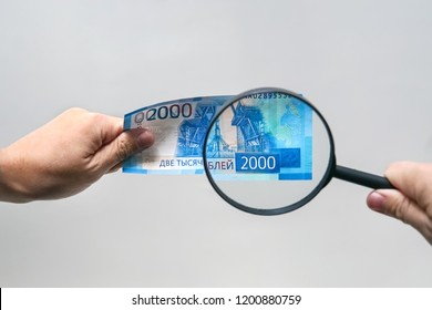 Russian currency, including new 2000 rouble bills. men's hands hold 2000 rubles and a magnifying glass. verification of the authenticity of the Russian banknote