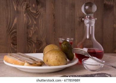 Russian dinner. Cowberry Vodka and Russian appetizer - lard, potatoes and salted cucumber on a rustic wooden background.